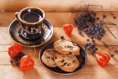 Biscuits et café de farine d'avoine au soleil sur un fond en bois avec le physalis et les baies sauvages de forêt Photos stock