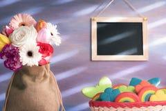 Biscuits et fleurs colorés avec un tableau Photographie stock libre de droits