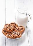 Biscuits et lait de chocolat dans la cruche sur le bois blanc Photographie stock