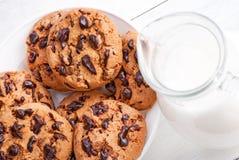 Biscuits et lait de chocolat dans la cruche sur le bois blanc Photographie stock libre de droits