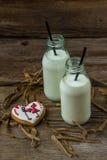 Biscuits et lait de Valentine dans une bouteille sur un fond en bois Photo stock