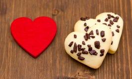 Biscuits et petit coeur rouge sur le bois Images stock