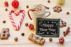 Biscuits et tableau noir de Noël avec la décoration de fête sur le bois Image libre de droits