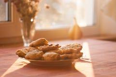Biscuits fabriqués à la main cuits au four du plat sur la table au soleil brillant Photographie stock libre de droits