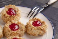 Biscuits faits à partir de la tarte sablée de noisette avec l'intérieur de confiture de fraise sur un plat blanc avec une fourche photos stock
