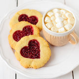 Biscuits faits maison avec le centre en forme de coeur et une tasse de Choco chaud Images stock
