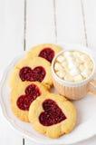 Biscuits faits maison avec le centre en forme de coeur et une tasse de Choco chaud Image stock
