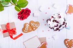 Biscuits faits maison dans la forme du coeur avec amour vous lettrage sur la table en bois blanche avec la carte de voeux, la fle Photographie stock libre de droits