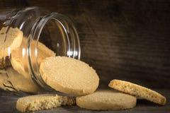 Biscuits faits maison de beurre débordant le pot en verre Photo stock