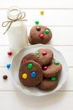 Biscuits faits maison de chocolat décorés des baisses colorées de sucrerie et de la bouteille de lait photos libres de droits