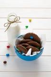 Biscuits faits maison de chocolat décorés des baisses colorées de sucrerie et de la bouteille de lait images stock