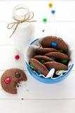 Biscuits faits maison de chocolat décorés des baisses colorées de sucrerie et de la bouteille de lait photo libre de droits
