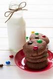 Biscuits faits maison de chocolat décorés des baisses colorées de sucrerie et de la bouteille de lait images libres de droits