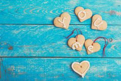 Biscuits faits maison de forme de coeur sur le fond bleu, VOUS J'AMOUR Photographie stock libre de droits