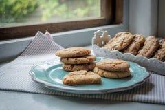 Biscuits faits maison de gingembre d'un plat à une fenêtre Photos libres de droits