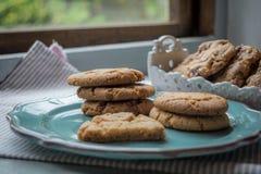 Biscuits faits maison de gingembre d'un plat à une fenêtre Images libres de droits