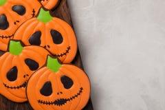 Biscuits faits maison de gingembre sous forme de potirons pour Halloween Sur le fond concret plus clair Vue supérieure avec l'esp Photo stock