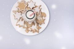 Biscuits faits maison de pain d'épice de Noël sur la bouteille en verre étendue plate de concept de vacances de fond bleu-clair a photographie stock