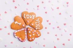 Biscuits faits maison sous forme de coeur avec letteing je t'aime avec des coeurs de sucrerie de sucre de bonbons sur le fond bla Photographie stock
