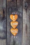 Biscuits faits maison sous forme de coeur avec letteing je t'aime et de coeurs de sucrerie de sucre de bonbons sur le fond en boi Photographie stock libre de droits