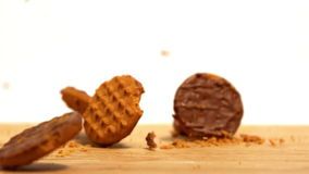 Biscuits falling and breaking on wooden table stock video