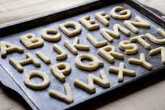 Biscuits formés par lettre d'alphabet sur le plateau de cuisson photo libre de droits