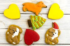 Biscuits in the form of dogs, hearts, fir trees and bones. Christmas composition. White background Royalty Free Stock Photo