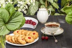 Biscuits frais de thé avec des cerises images stock