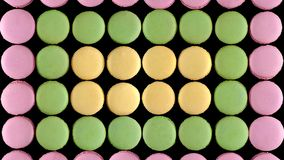 Biscuits français colorés doux de macaron sur le fond foncé, vue supérieure photo stock