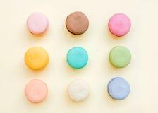 Biscuits français colorés doux de macaron sur le fond jaune en pastel Images stock