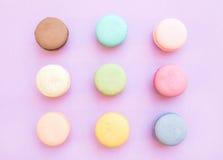 Biscuits français colorés doux de macaron sur le fond lilas en pastel Photographie stock