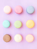 Biscuits français colorés doux de macaron sur le fond lilas en pastel Photos libres de droits