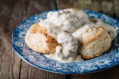 Biscuits and gravy. On blue vintage plate and wooden rustic surface royalty free stock photography