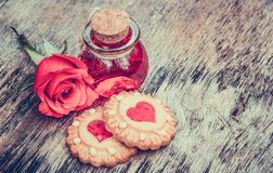 Biscuits with hearts and love elixir. Valentine`s Day. Set for lovers. Sweet poison. Philtre in round bottle. Copy space stock photography