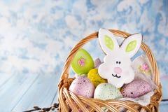 Biscuits, lapins et oeufs de Pâques dans un panier sur le fond bleu-clair Images stock