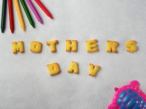 Biscuits, letters, shapes and colorful crayons,plastic toys arranged on a white background for Mother`s Day royalty free stock photos