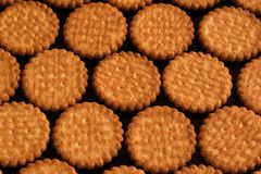 Biscuits lying in rows on a black lacquered surface. Close-up Stock Photography