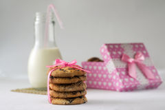 Biscuits with milk and chocolate box. Biscuits with milk and piece of chocolate on the bamboo with a bow of pink ribbon box heart Stock Photos