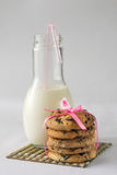 Biscuits with milk and chocolate. Biscuits with milk and piece of chocolate on the bamboo with a bow of pink ribbon Stock Photography