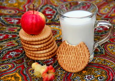 Biscuits and Milk. Organic apples, biscuits and mug of milk on colorful tablecloth Royalty Free Stock Photos