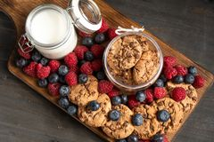 Biscuits and mixed forest fruits placed on wooden board. stock photography