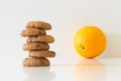 Biscuits ou fruit, biscuits brouillés, oranges au foyer, concept de choix de régime photographie stock