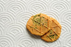 Biscuits on paper place-mat. Two pieces of biscuits on a patterned paper place-mat Royalty Free Stock Photos