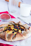 Biscuits with peach and blueberry on a white table. With a glass of milk Royalty Free Stock Image