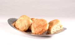 Biscuits on a Plate. 4 biscuits on a metal bread serving dish photographed on a white background Royalty Free Stock Photo