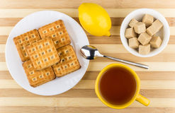 Biscuits in plate, cup of tea, bowl of lumpy sugar Royalty Free Stock Photos