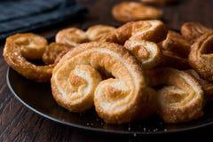 Biscuits plus palmier dans le plat noir sur la surface en bois Image libre de droits