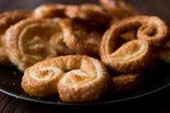 Biscuits plus palmier dans le plat noir sur la surface en bois Images libres de droits