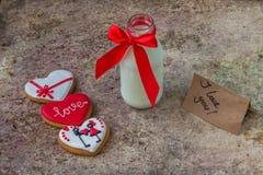 Biscuits pour le jour du ` s de Valentine et bouteille en verre de lait avec le ri rouge Image libre de droits