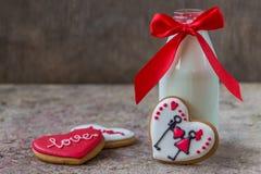 Biscuits pour le jour du ` s de Valentine et bouteille en verre de lait avec le ri rouge Images stock